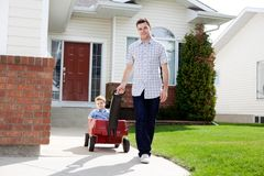 Father Pulling Son Sitting Inside Wagon. Father pulling son in a wagon in front of house on sidewalk Royalty Free Stock Images