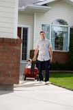 Father Pulling Son Sitting in Pram. Father pulling son sitting with a ball in pram down a walkway Stock Photos