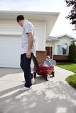 Father Pulling Son Sitting in Wagon. Father pulling son in wagon in front of house Royalty Free Stock Photography