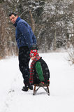 Father pulling son on sledge. Portrait of father and son in the snow royalty free stock image