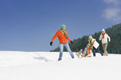 Father pulling wife on sled through snow as children push Stock Photos