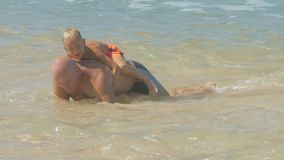 Father pushes up with little son on back in ocean water. Strong father pushes up with little son sitting on back in clear ocean water on sunny day slow motion stock footage