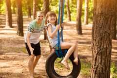 Father pushing child daughter on tire swing in summer forest. family weekend