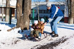 Father pushing children down the hill in a sled Stock Photo