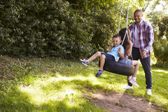 Father Pushing Children On Tire Swing In Garden Stock Photos