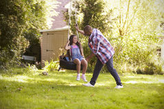 Father Pushing Daughter On Tire Swing In Garden Royalty Free Stock Image