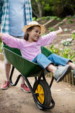 Father pushing daughter in wheelbarrow Stock Images