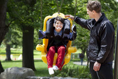 Father pushing disabled boy in special needs swing. Father pushing disabled boy in special needs handicap swing. Child has cerebral palsy royalty free stock photo