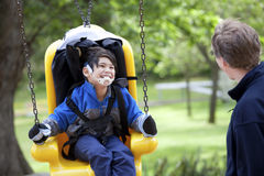 Father pushing disabled son on handicap swing royalty free stock photography