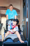 Father pushing disabled son in wheelchair out the front door Royalty Free Stock Images