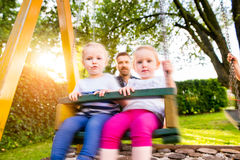 Father pushing his daughters on swing in a park. Stock Image