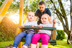Father pushing his daughters on swing in a park. Stock Photos