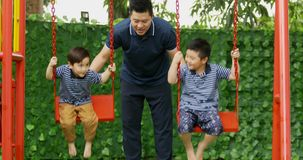 Father pushing his sons on swing stock video footage