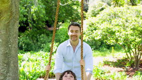 Father pushing his young son on a swing stock footage