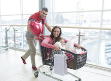 Father pushing mother and young daughter in shopping trolley Royalty Free Stock Image