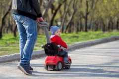 Father pushing a red push car with his toddler son riding it on a spring walk. Dad and son walk together. Father pushes a red push car with toddler son riding it royalty free stock photos