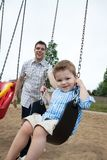 Father Pushing Son on Swing. Happy father pushing his son on a swing Stock Image