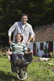 Father Pushing Son In Wheelbarrow Outside Cottage Stock Photography