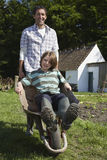 Father Pushing Son In Wheelbarrow Outside Cottage Royalty Free Stock Photography