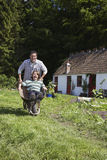 Father Pushing Son In Wheelbarrow Outside Cottage Royalty Free Stock Image