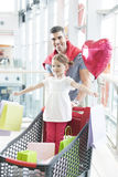 Father pushing young daughter in shopping trolley with shopping bags Royalty Free Stock Images