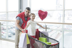 Father pushing young daughter in shopping trolley with shopping bags Stock Images