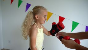 Father put boxing gloves on child hands. Daddy and daughter learn self defense