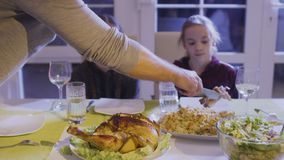 Father put a chicken thigh on daughter`s plate. Man holds a wooden fork and knife and cuts a delicious fried chicken. Two little daughters observes after the man stock footage