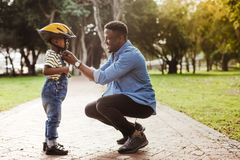 Father puts his son a helmet for riding bike. African men putting helmet on cute boy at the park. Father puts his son a protective helmet for riding bike stock photos