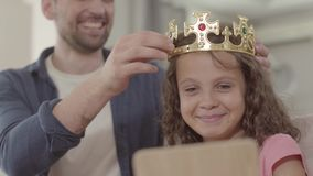 Portrait father putting the crown on the head of curly girl looking in the mirror. Daddy adores his daughter. Father. The father putting the crown on the head of stock video footage