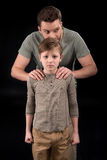 Father putting hands on shoulders of scared little son. Family problems concept Royalty Free Stock Photos
