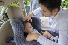 Father putting his baby on the car seat Stock Image