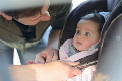 A father putting his baby daughter into her car seat. In the car Stock Photo