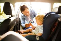 Father putting his son in the car. Royalty Free Stock Photo