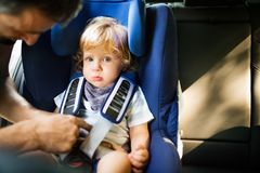 Father putting his son in the car. Stock Image