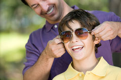 Father putting sunglasses on son Royalty Free Stock Photography