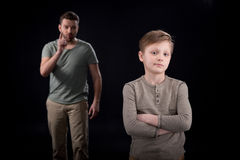 Father quarreling at indifferent son standing with crossed arms Stock Image