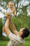 Father raising son in air Royalty Free Stock Image