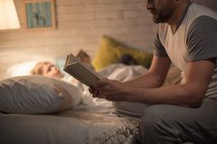 Father Reading Bedtime Story to Son. Side view portrait of men reading bedtime story to little son sitting on edge of bed in dim light with blurred shape of Stock Image