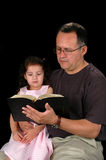 Father reading bible to child