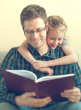 Father reading book with daughter. Stock Image