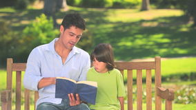 Father reading a book with his son. While sitting on a park bench stock footage