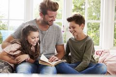 Father Reading Book With Son And Daughter At Home stock photos