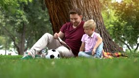 Father reading book with son in park, preparing homework together, parenting. Stock photo stock images