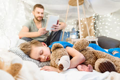 Father reading book to cute little boy sleeping with teddy bear Stock Photography