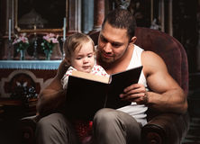 Father reading book to daughter. Indoors Royalty Free Stock Photo