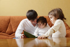 Father reading book to daughters Stock Photography