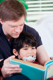 Father reading book to disabled little son Royalty Free Stock Photography