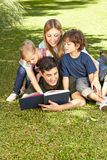 Father reading book to family. And his two children in a garden royalty free stock photo