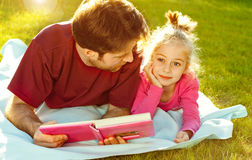 Father reading a book to his daughter in the garden. Father reading a book to his daughter while laying outdoor on the grass in the garden during sunset Stock Photo